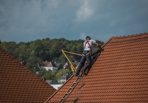 roofer on a roof checking tiles.