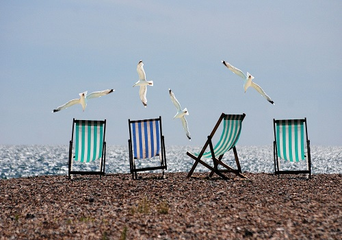 4 sunbeds on a beach with seagulls flying over them, while the sun is shining.