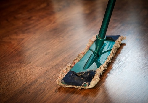 A mop resting on a brown wooden floor.