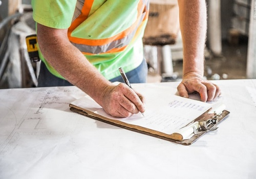 A construction worker writing on a piece of paper.