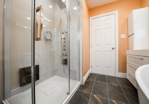 A bright bathroom with a large shower area and a sparkling clean shower screen