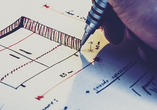 A hand holding a pen and drawing up a plan for home renovation projects you can do over the weekend