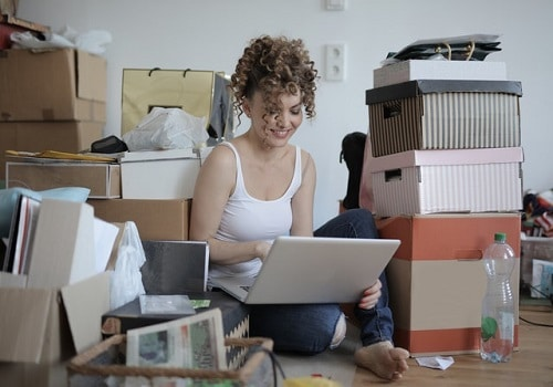 Girl typing on a laptop in a messy room full of boxes.