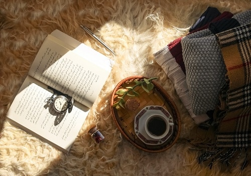 A book, a cup of coffee, and a few pieces of clothes on the shaggy rug.